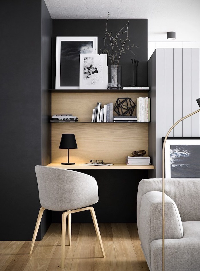 black-wall-wooden-bookshelves-grey-chair-sofa-desk-lamp-home-office-setup-books-paintings